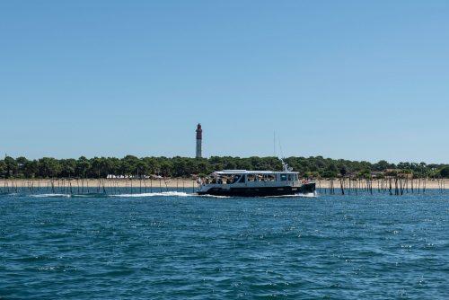 Un bateau de l'UBA passant devant le phare du Cap Ferret lors du Grand Tour de l'Île aux Oiseaux